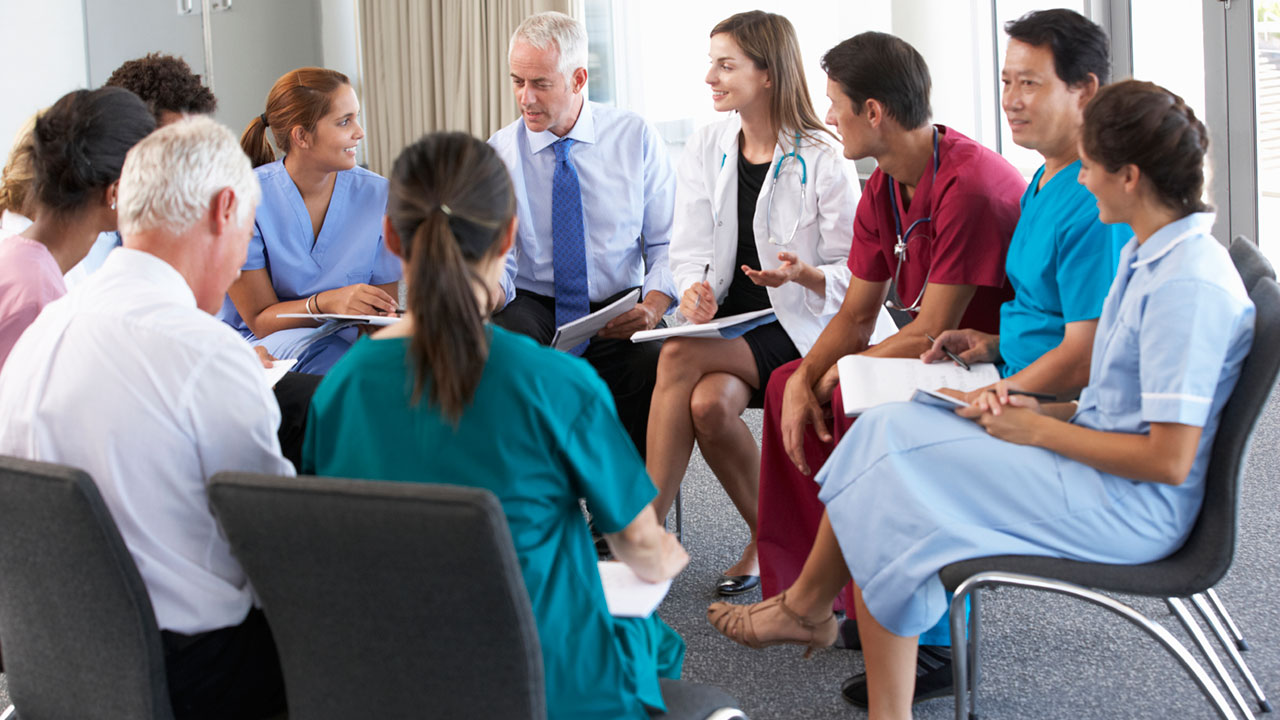 Medical-Staff-Seated-In-Circle-At-Case-Meeting-slider